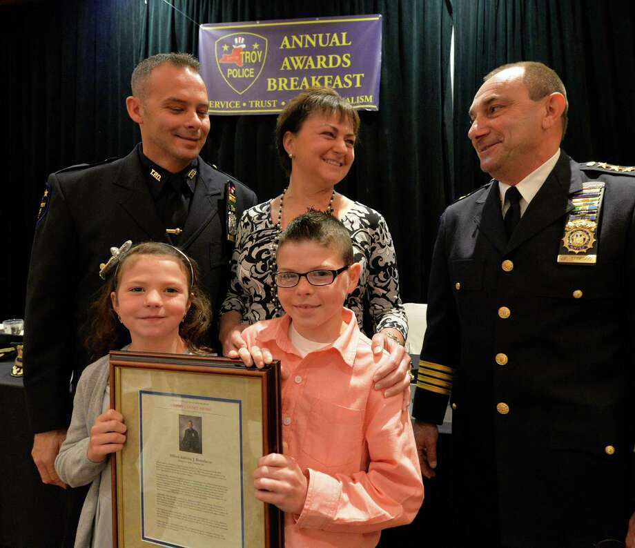 Troy police officer Anthony J. Buttofucco, left, received the 2013 John J. Giveny Award during the City of Troy Police 2014 Awards Breakfast Monday morning May 19, 2014 in Troy, N.Y.  Officer Buttofucco is joined at the ceremony by his wife, Jennifer, and two children, Isabella, 7, and Anthony ,9. Presenting the award is Troy Police Chief John  Tedesco.  (Skip Dickstein / Times Union) Photo: SKIP DICKSTEIN / 00026938A