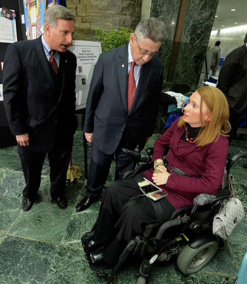 Assemblyman David Wepren, Queens, left, joins Assembly Speaker Shelly Silver, center, in greeting Kim Hill, director of the task force for people with disabilities, at the Assembly Disabilities Awareness Day Monday morning, May 19, 2014, in the well of the Legislative Office building in Albany, N.Y.  (Skip Dickstein / Times Union) Photo: SKIP DICKSTEIN / 00026944A
