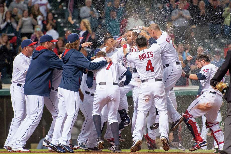 Cleveland's Michael Brantley, center, is all but covered up by his water-dousing teammates as he crosses home plate after his home run in the bottom of the 10th inning lifted the Indians to a 4-3 win over Detroit. Photo: Jason Miller, Stringer / 2014 Getty Images