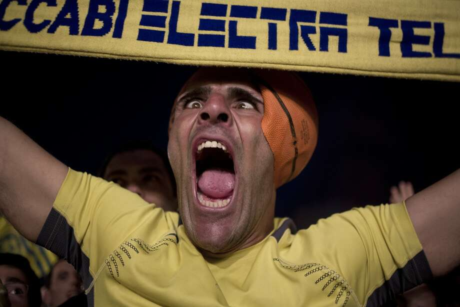 Our hoops are INSANE! In Tel Aviv, a Maccabi Tel Aviv fan celebrates his team's stunning victory in the Euroleague basketball championship. Tens of thousands of Maccabi supporters thronged a central square in the city after the upset over Real Madrid in Milan. Photo: Ariel Schalit, Associated Press