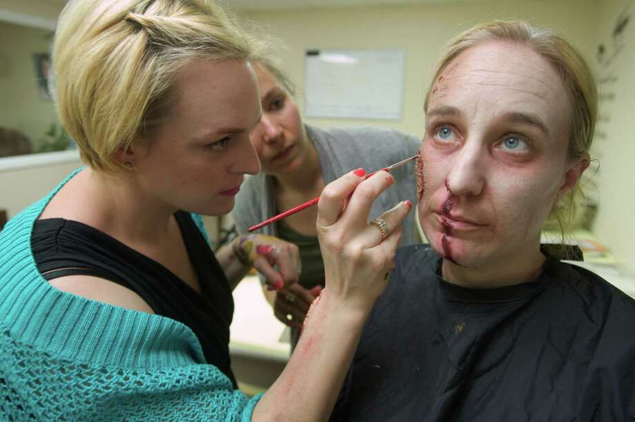 "Allison L. Sammel, 32, of Danbury, owner of La Bella School in Bethel, Conn, demonstrates how to blend a latex prosthetic into a face for Jessica Mercier, 28, of Hartford, who was creating a ""Ghoul"" for class, on Monday, May 19, 2014. Sammel's teaches students to be makeup artists and stylists. Her monday night class is for theater, film, and television techniques in special effect makeup. The subject, Bernadette Gulyas, 36, of Norwalk, is Sammel's sister-in-law, who volunteered for the night. Photo: H John Voorhees III / The News-Times Freelance"