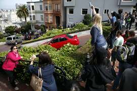 Tourists take pictures from the top of Lombard St. at Hyde St. in San Francisco, CA, Saturday May 17, 2014. Due to neighbor complaints of overcrowding, the SFMTA is proposing a pilot program that would shut down Lombard St. from Larkin to Leavenworth, for four weekends in the height of the summer tourist season.