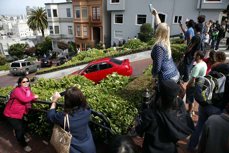 A crowd takes pictures from Hyde Street at the top of crooked Lombard Street, a major tourist attraction, where residents are complaining about the crush of tourists and cars. Photo: Michael Short, The Chronicle