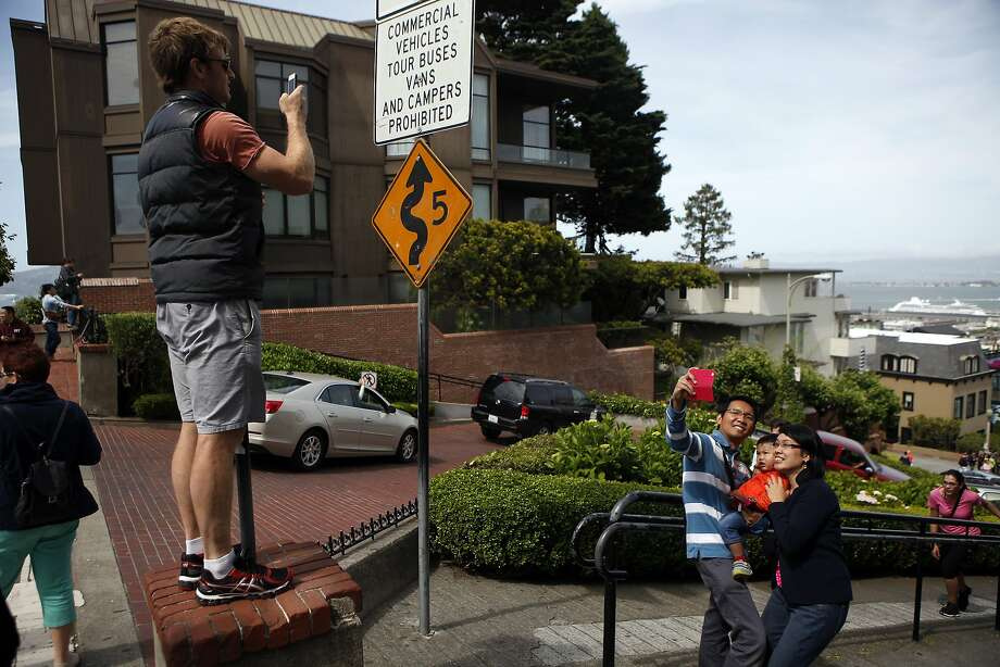 In this file photo, tourists take pictures from the top of Lombard St. at Hyde St. in San Francisco. Photo: Michael Short, The Chronicle
