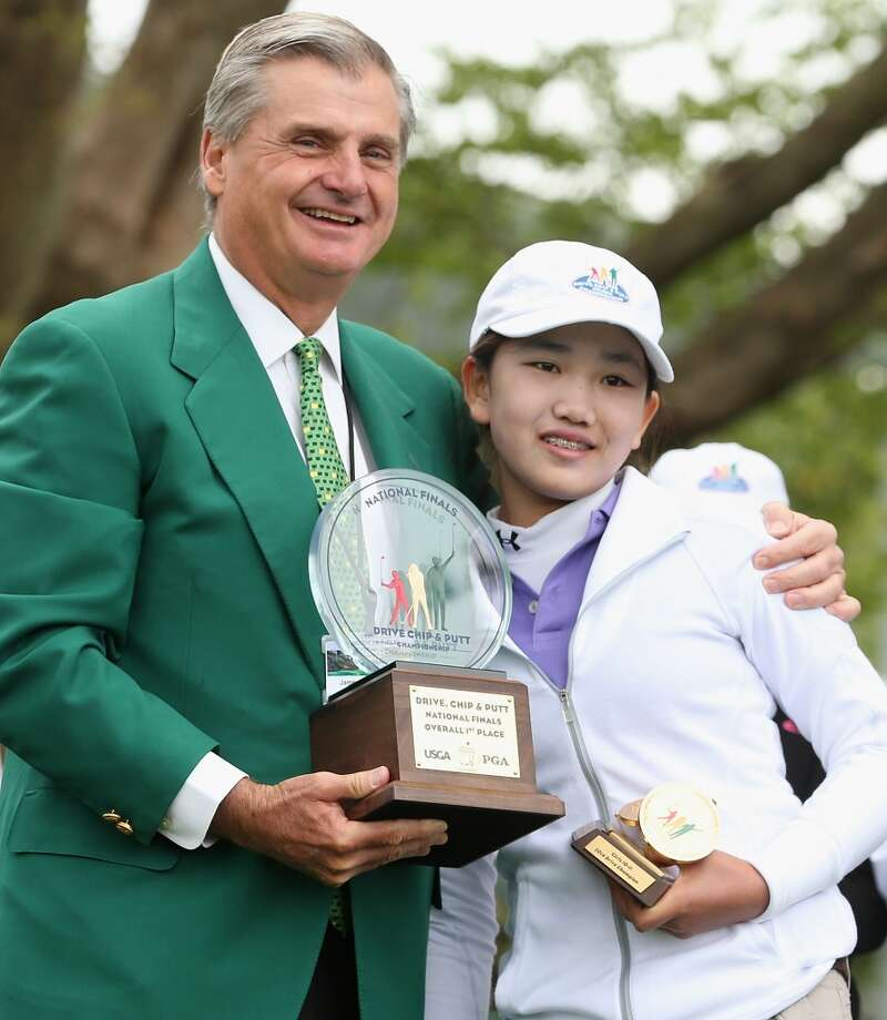 Lucy Li of Southern California receives her trophy from an Augusta National member after winning the Girls 10-11 category at the National Finals of the Drive, Chip and Putt Championship at Augusta National Golf Club on April 6, 2014 in Augusta, Georgia. Photo: Andrew Redington, Getty Images