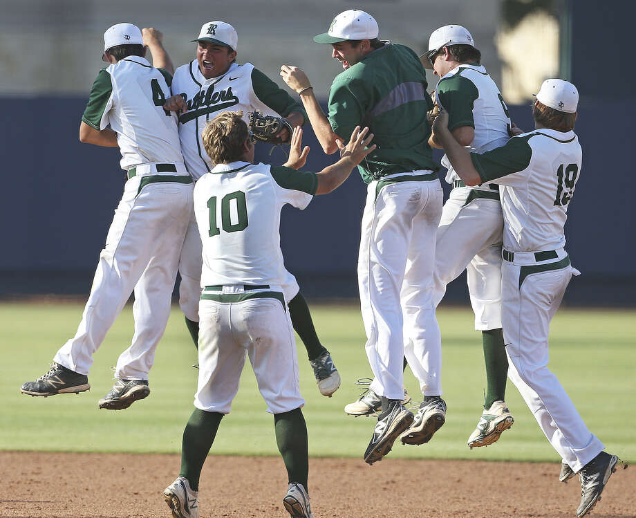 Rattler players storm the field after taking the series as Reagan plays Corpus Christi King in 5A regional quarterfinal baseball at UTSA on May 17, 2014. Photo: Tom Reel / San Antonio Express-News