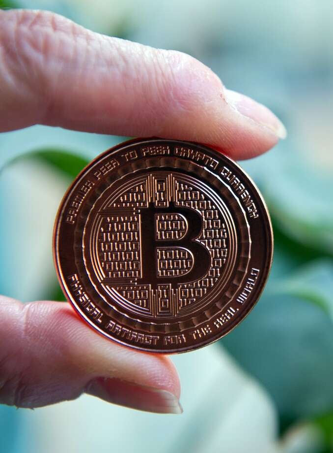 This May 1, 2014 photo taken in Washington, DC shows a bitcoin medal. Bitcoin uses peer-to-peer technology to operate with no central authority or banks; managing transactions and the issuing of bitcoins is carried out collectively by the network. The Massachusetts Institute of Technology (MIT) announced on April 29, 2014 it would give $100 in Bitcoin to its 4,500 students starting in the Fall of 2014. The project started by two MIT students aims for a better understanding of emerging technologies.     AFP PHOTO / Karen BLEIERKAREN BLEIER/AFP/Getty Images Photo: Karen Bleier, AFP/Getty Images