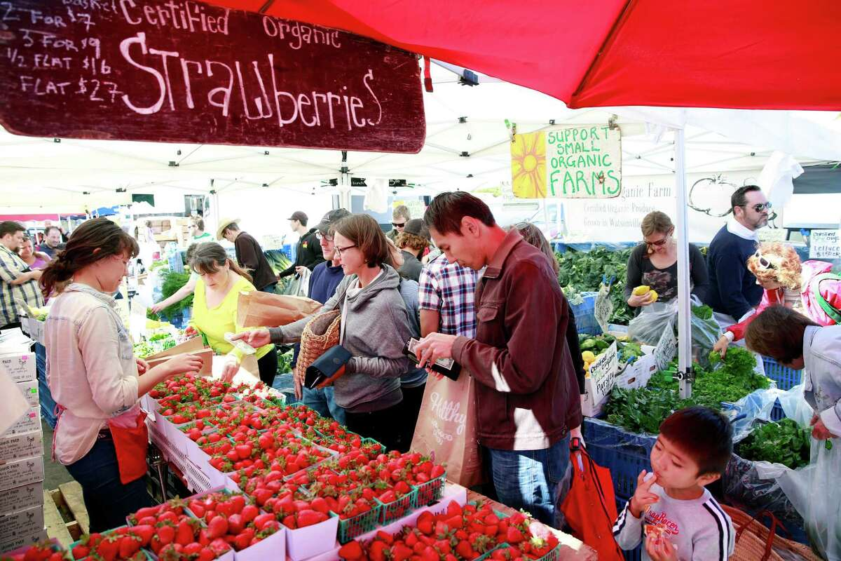 Strawberries flood farmers' markets in spring as evidence by the Tomatero Farm's stand at the Marin County farmers market at the Marin Civic Center in San Rafael in May 2014. Apples, squash, nuts and chard are typical fare in October. Shoppers are urged to learn what's freshly harvested and buy in season.