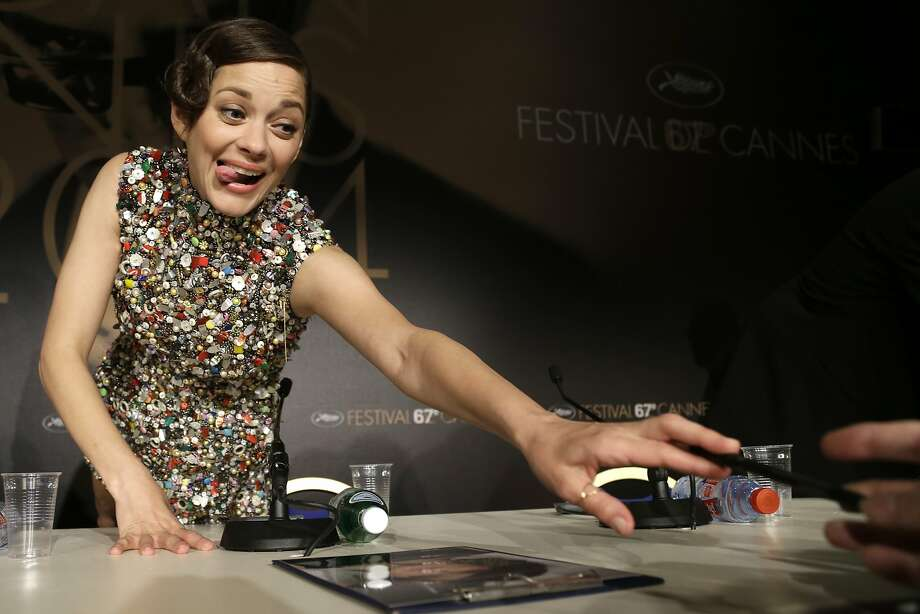 "Accommodating autographs:Signing photos at Cannes is exhausting work for actress Marion Cotillard, the star of ""Two Days, One Night."" Photo: Thibault Camus, Associated Press"