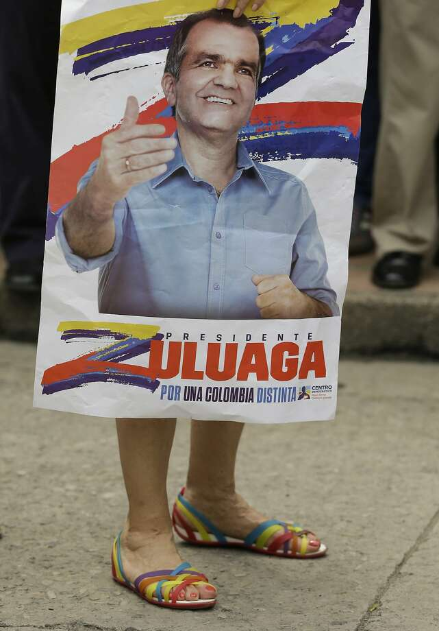 He's taller than he looks in his photos:A woman carries a campaign poster for Democratic Center presidential candidate Oscar Ivan Zuluaga during a campaign rally in Villeta, Colombia. Colombians will vote for a president May 25. Photo: Fernando Vergara, Associated Press