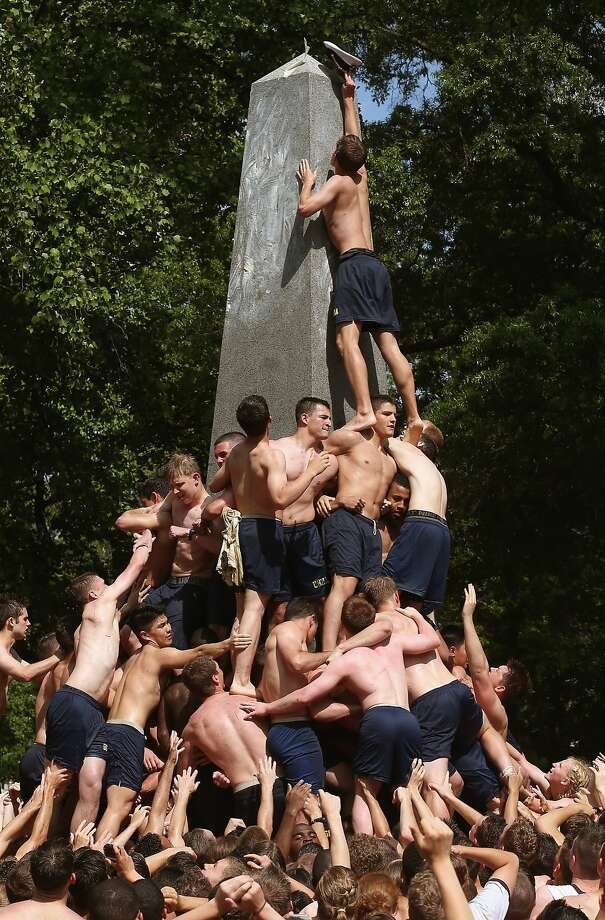 Greasy lid stuff:At the Naval Academy in Annapolis, a plebe puts an officer's hat on top of the lard-covered Herndon   Monument, replacing a plebian sailor's cap. The hat swap is an end-of-the-year tradition for the freshmen. Photo: Mark Wilson, Getty Images