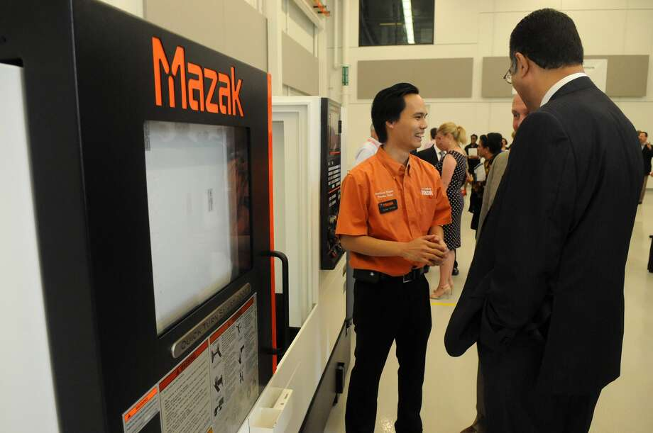Dung Pham, an applications engineer with Mazak Corp. in Houston, talked to visitors at the opening of the new Lone Star College-University Park Energy and Manufacturing Institute Building. Photo: Jerry Baker, Freelance