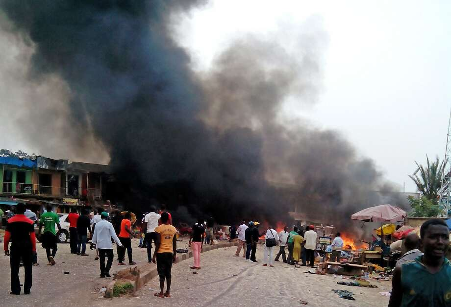 Smoke rises after a bomb blast at a bus terminal in Jos, Nigeria, Tuesday, May 20, 2014. Two explosions ripped through a bustling bus terminal and market frequented by thousands of people in Nigeria's central city of Jos on Tuesday afternoon, and police said there are an unknown number of casualties. The blasts could be heard miles away and clouds of black smoke rose above the city as firefighters and rescue workers struggled to reach the area as thousands of people fled. (AP Photo/Stefanos Foundation) Photo: Associated Press