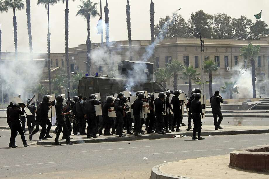 Riot police fire tear gas towards supporters of the Muslim Brotherhood during a demonstration at Cairo University hours after a drive-by shooting killed several Egyptian policemen and wounded others during an overnight rally by Islamist students at another university, in Cairo, Egypt, Monday, May 20, 2014. A statement from an Al-Azhar student movement said the shooting took place after their rally had ended. The attack at Al-Azhar University raises security concerns ahead of presidential elections next week. (AP Photo/Ahmed Gamil) Photo: Ahmed Gamil, Associated Press