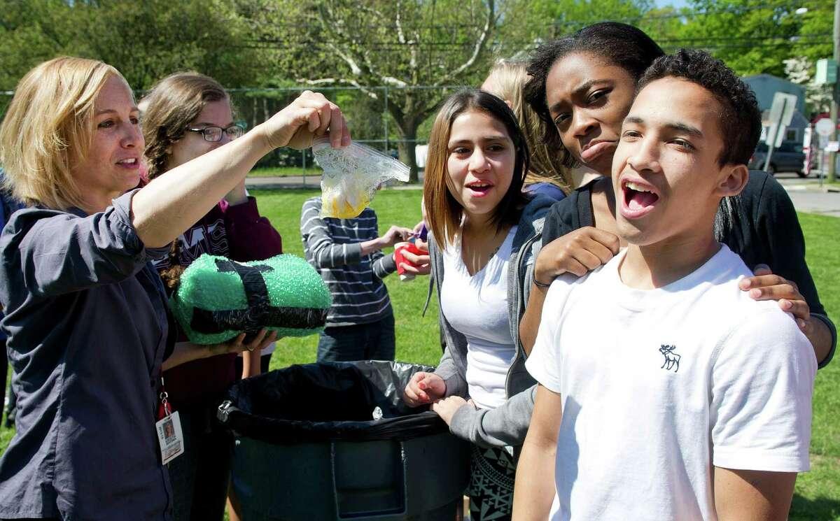 Science teacher Kristin Bivona holds up Gerardo Maradiaga's broken egg as he reacts to his failed