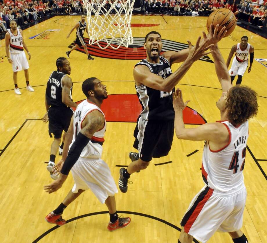 San Antonio Spurs' Tim Duncan shoots between Portland Trail Blazers' LaMarcus Aldridge (left) and Robin Lopez during second half action of Game 3 in the Western Conference semifinals Saturday May 10, 2014 at the Moda Center in Portland, OR. The Spurs won 118-103. Photo: Edward A. Ornelas, San Antonio Express-News