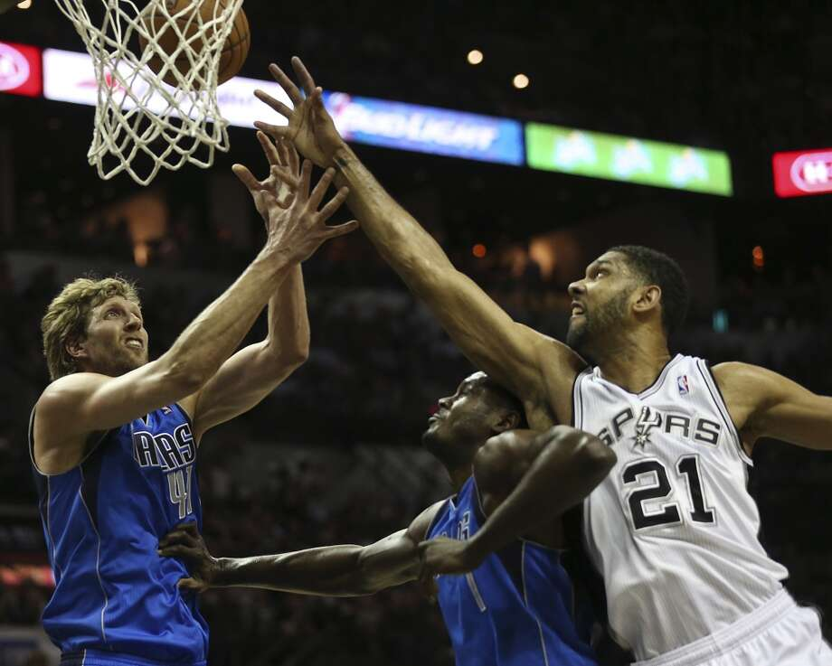 San Antonio Spurs' Tim Duncan goes over Dallas Mavericks' Samuel Dalembert for a rebound as Dirk Nowitzki reaches in during the first half of game seven in the first round of the Western Conference Playoffs at the AT&T Center, Sunday, May 4, 2014. Photo: Jerry Lara, San Antonio Express-News