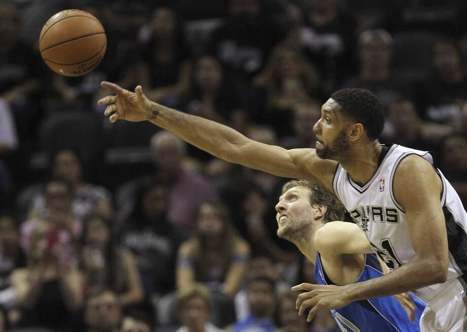 San Antonio Spurs' Tim Duncan goes over Dallas Mavericks' Dirk Nowitzki for a rebound during the second half of game seven in the first round of the Western Conference Playoffs at the AT&T Center, Sunday, May 4, 2014. The Spurs won, 119-96 to move on to the conference semi-finals against the Portland Trailblazers. Photo: Jerry Lara, San Antonio Express-News