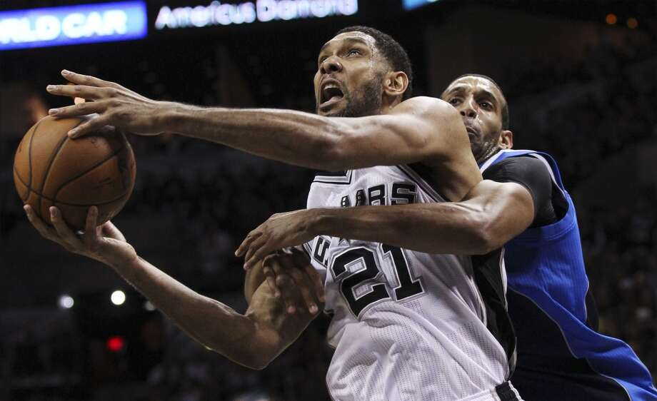 Spurs' Tim Duncan (21) gets wrapped up by Dallas Mavericks' Brandan Wright (34) in the second half of Game 5 of the first round of the Western Conference playoffs at the AT&T Center on Wednesday, Apr. 30, 2014. Spurs defeated the Mavericks, 109-103. (Kin Man Hui/San Antonio Express-News) Photo: Kin Man Hui, San Antonio Express-News