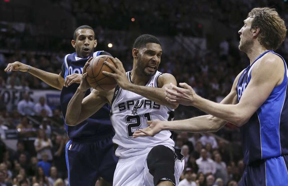 San Antonio Spurs' Tim Duncan gets the rebound between Dallas Mavericks' Brandan Wright, left, and Dirk Nowitzki during the second half of game five in the first round of the Western Conference Playoffs at the AT&T Center, Wednesday, April 30, 2014. The Spurs won 109-103 to lead the series, 3-2. Photo: Jerry Lara, San Antonio Express-News