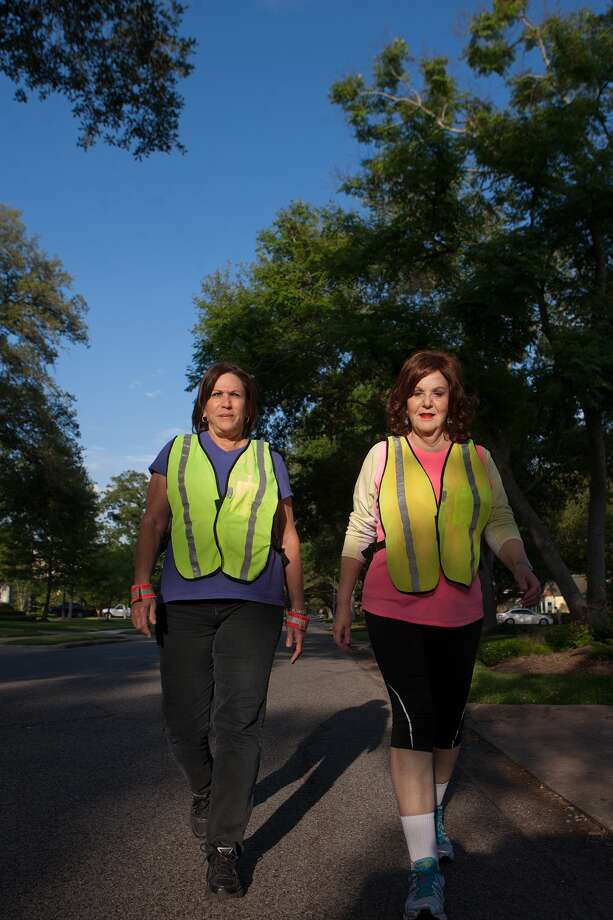 Bellaire residents Cathy Jankovic, left, and Glenda Danburg Waldman demonstrate how reflective gear makes them more visible. Waldman says the city's sidewalks often have gaps or uneven surfaces that result in walkers and runners getting in the streets. Photo: R. Clayton McKee, Freelance / © R. Clayton McKee