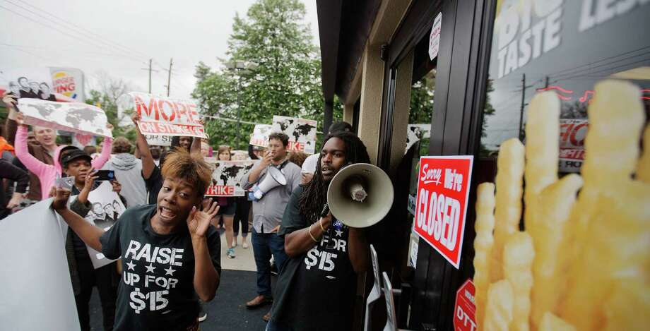 Protesters outside a fast-food restaurant call for higher wages. Investors, in fear of global PR nightmares, are speaking out on the income inequality issue, too. Photo: David Goldman / Associated Press / AP