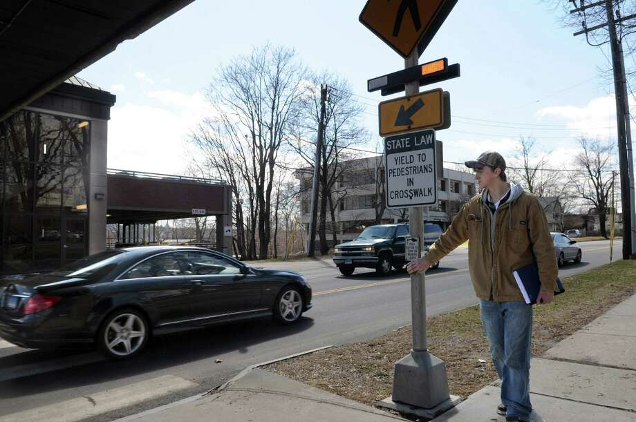 A student presses the button to stop cars at a crosswalk in front of Western Connecticut State University on White Street in Danbury earlier this Spring. Safety improvements have been made on White Street as a response to the death of a student killed crossing the street in 2011. Photo: Carol Kaliff / The News-Times