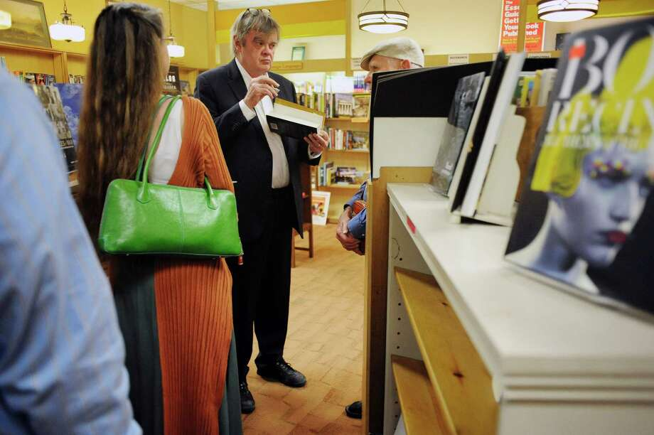 "Garrison Keillor, center, author and host of ""A Prairie Home Companion,"" talks with a fan during a book signing Tuesday, May 20, 2014, at the Book House of Stuyvesant Plaza in Albany, N.Y. (Paul Buckowski / Times Union) Photo: Paul Buckowski / 00026955A"