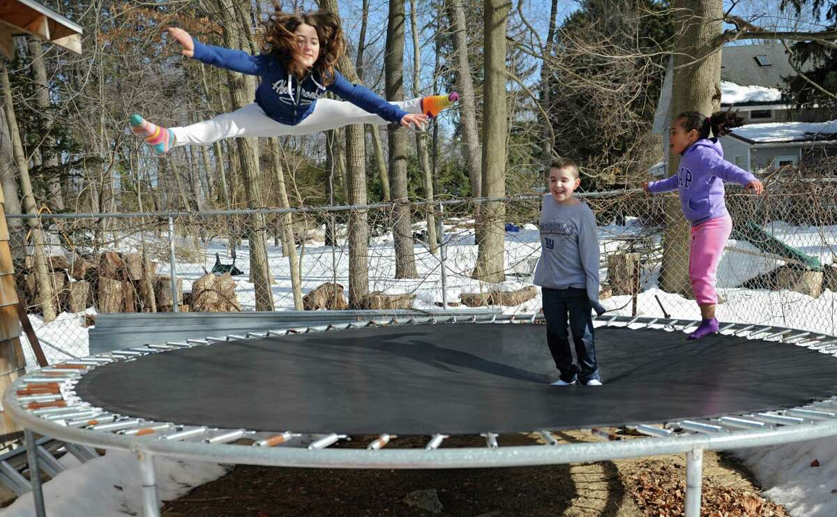 From left, Julia Skladzinski, 10, Sean Rogers, 9, and Sophie Adkison, 4, jump for joy in the warmer weather on a trampoline in back of a home on Norwood St. on Friday, March 7, 2014 in Guilderland, N.Y. (Lori Van Buren / Times Union)