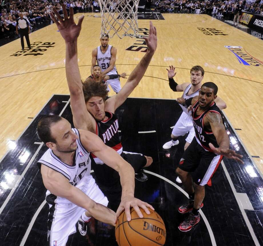 San Antonio Spurs' Manu Ginobili looks to pass around Portland Trail Blazers' Robin Lopez and LaMarcus Aldridge during second half action of Game 2 in the Western Conference semifinals Thursday May 8, 2014 at the AT&T Center. The Spurs won 114-97. Photo: Edward A. Ornelas, San Antonio Express-News