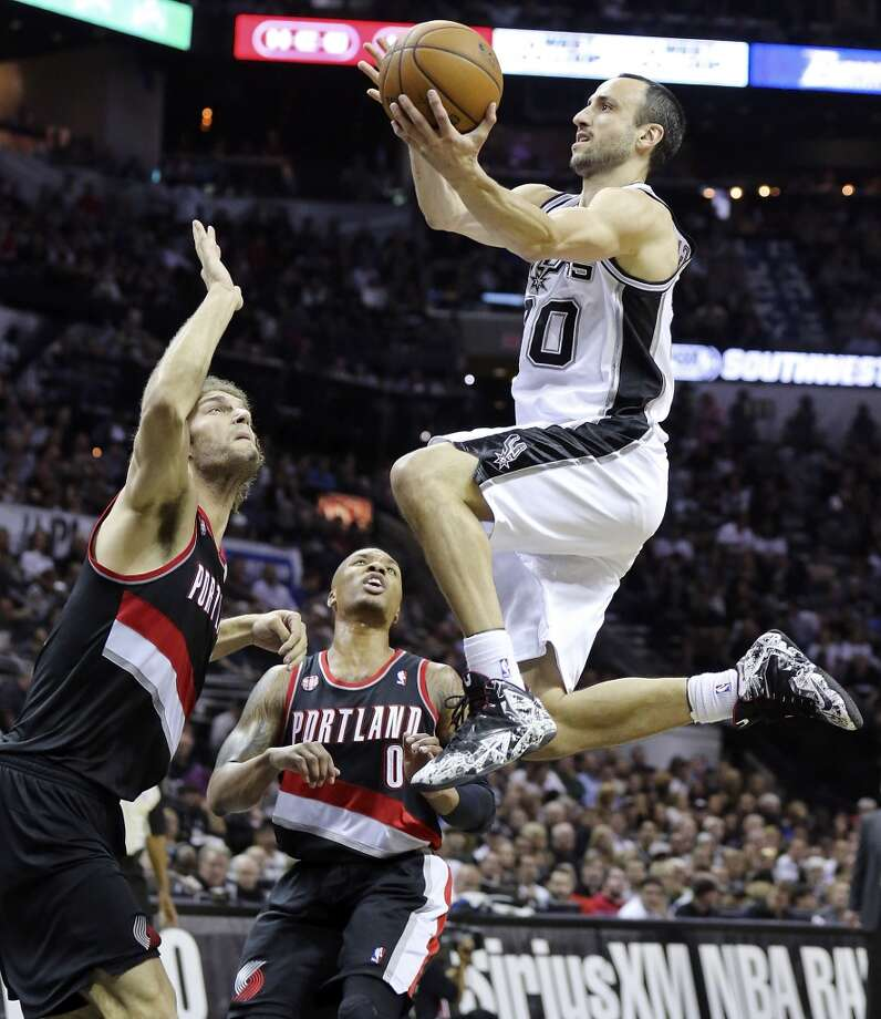 San Antonio Spurs' Manu Ginobili drives to the basket against Portland Trail Blazers' Robin Lopez and Portland Trail Blazers' Damian Lillard during first half action of Game 2 in the Western Conference semifinals Thursday May 8, 2014 at the AT&T Center. Photo: Edward A. Ornelas, San Antonio Express-News