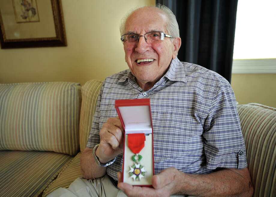 D-Day veteran Irving Glazer, 92, displays the Legion of Honor medal that he recently received from the French government at his home in Shelton, Conn. on Tuesday, May 20, 2014. Glazer landed under fire at Utah Beach, where was tasked with detecting German landmines. Photo: Brian A. Pounds / Connecticut Post