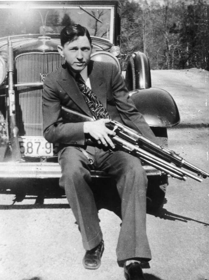 Clyde Barrow holding a rifle and a shotgun while sitting on the front fender of a car, circa 1933. Photo: Hulton Archive, Getty Images / Archive Photos