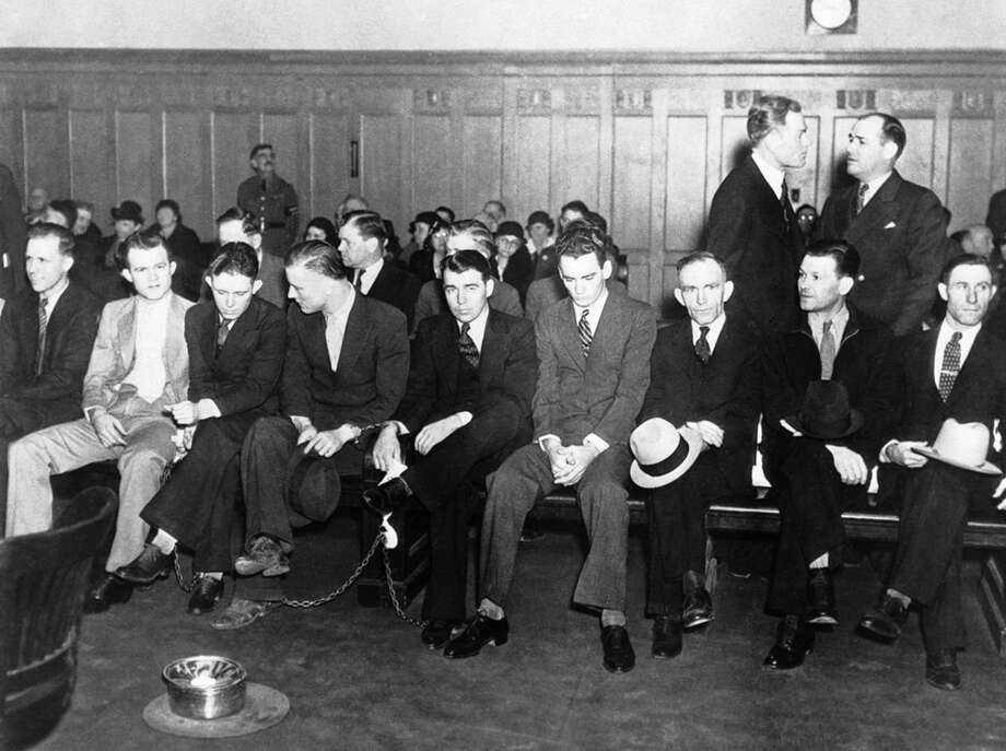 Nine of the 23 people brought to trial on charges of harboring the late Clyde Barrow and his companion Bonnie Parker, are shown in court, some of them with chains on their ankles, Feb. 22, 1935 in Dallas, Texas. From left to right: Floyd Garland, Hamilton S. J. Whatley, L.C. Barrow, Henry Methvin, William D. Jones, Joe Francis, James Mullen, Joe Chambless and Steve Davis. Photo: Associated Press