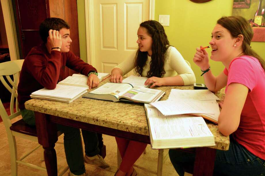 Abigail Jackson, 17, finds that studying takes on a different dimension when done with exchange students Carlos Iglesias, 17, of Spain and Caitlin Pretorius, 18, of South Africa. Photo: Jimmy Loyd / freelance