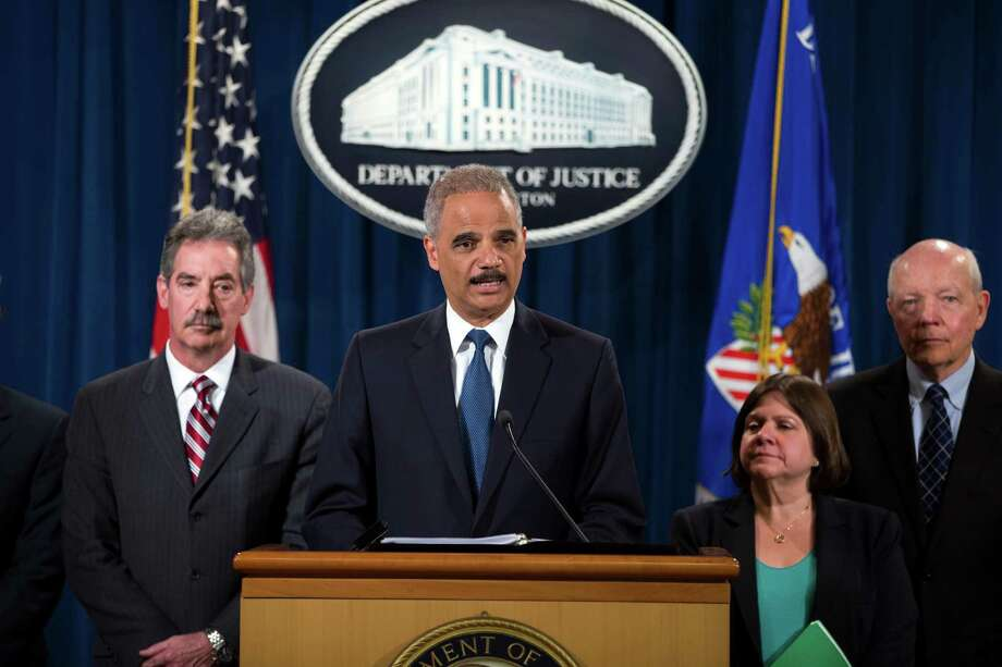 Attorney General Eric Holder, center, speaks during a news conference at the Justice Department, on Monday, May 19, 2014, in Washington. The Justice Department on Monday charged Credit Suisse AG with helping wealthy Americans avoid paying taxes through offshore accounts, and a person familiar with the matter said the European bank has agreed to pay about $2.6 billion in penalties. From left, Deputy Attorney General James Cole, Holder, Assistant Attorney General for the Tax Division Kathryn Keneally, and IRS Commissioner John Koskinen (AP Photo/ Evan Vucci) ORG XMIT: DCEV108 Photo: Evan Vucci / AP