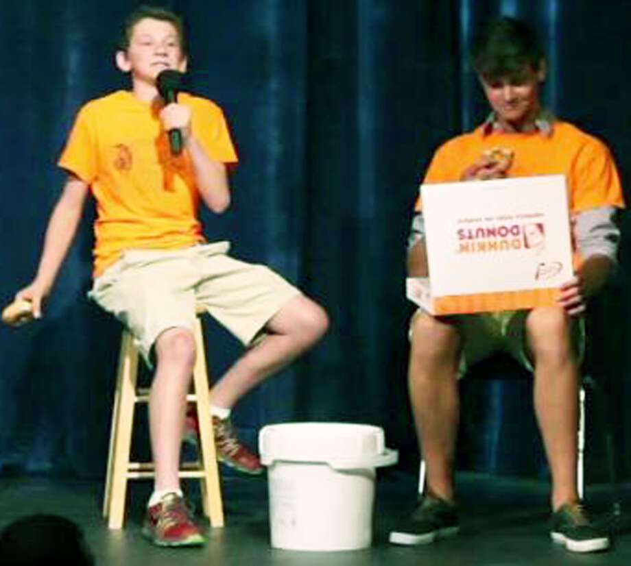 Sophomore Jack Day, left, and junior Logan Doud perform a poem about doughnuts during the recent Poetry Slam at New Milford High School.  Courtesy of New Milford High School Photo: Contributed Photo / The News-Times Contributed