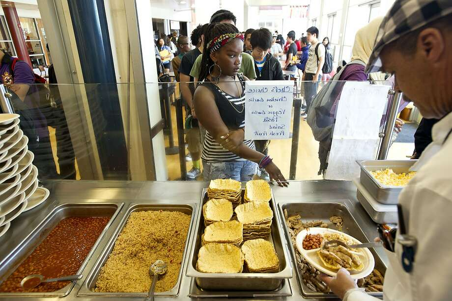 William Harris serves lunch at Berkeley High. Lunch rules require that students be served a helping of fruit or vegetables. Photo: Noah Berger, Special To The Chronicle