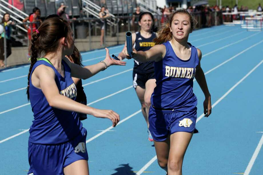 Bunnell High School's Jackie Williams pass the baton to team mate Ariel Smith during the 4x800 race at Tuesday afternoon track meet at Bunnell High School. Photo: Mike Ross / Mike Ross Connecticut Post freelance -www.mikerossphoto.com