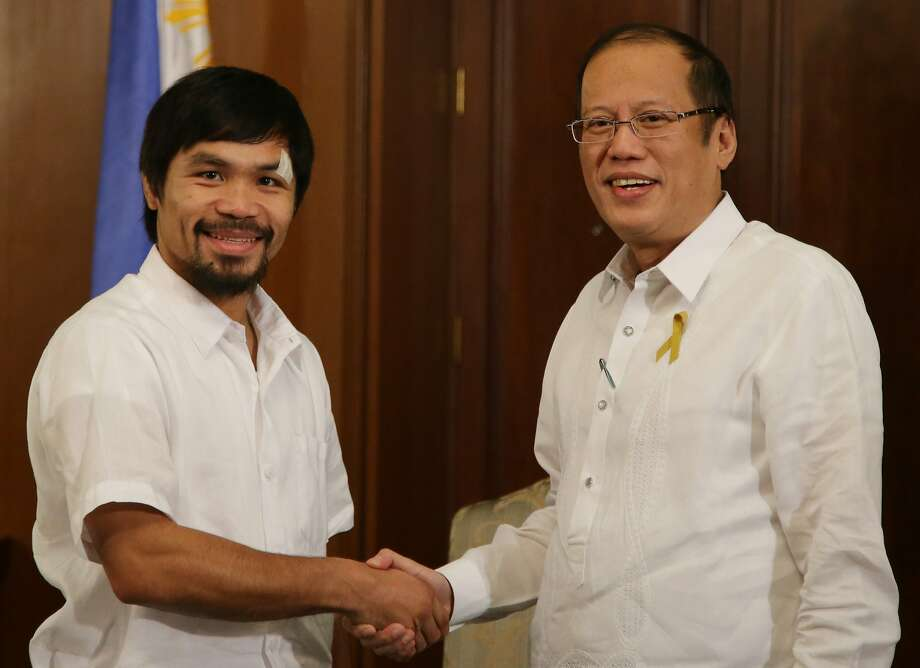 Filipino boxing hero and congressman Manny Pacquiao, left, shakes the hands of Philippine President Benigno Aquino III during his courtesy call at the Malacanang Presidential Palace in Manila Philippines on Monday, April 21, 2014. Pacquiao recently defeated American Timothy Bradley during their WBO welterweight title bout in Las Vegas. (AP Photo/Aaron Favila) Photo: Aaron Favila, Associated Press