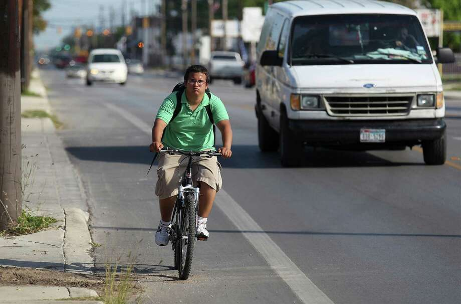 "Damien Van Atta, 17, rides his bike along South Flores Street in the bike lane on Tuesday, May 20, 2014. Van Atta said he bikes 15 miles from East Central High School where he is a student to visit his grandfather once a week. He believes the bike lanes offer safety and convenience for bicyclists. ""It (the bike lanes) gets you far enough away from cars and pedestrians,"" Van Atta said. A city council hearing on May 29 may remove the bike lanes along South Flores. Photo: Kin Man Hui, San Antonio Express-News / ©2014 San Antonio Express-News"