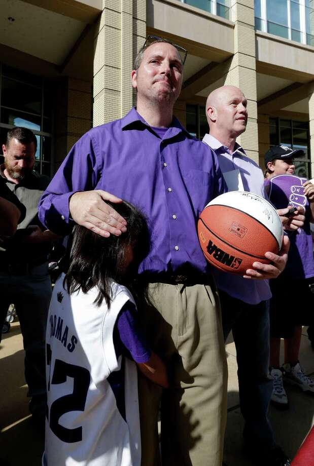 Sacramento Kings fan Jeff Braverman grimaces as he comforts his daughter, Lauren, 7, after learning that the Kings had received the eighth pick in the NBA basketball draft lottery, at a rally for the team outside Sacramento City Hall, Tuesday, May 20, 2014. The city council was scheduled to vote on a $477 million downtown arena for the team. (AP Photo/Rich Pedroncelli) Photo: Rich Pedroncelli, Associated Press / AP