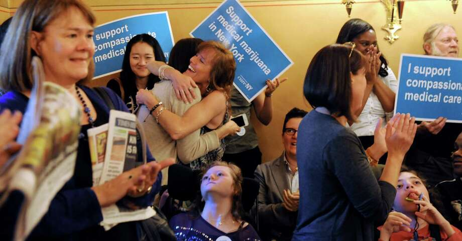 Kathy Annable of Marcellus, center, right, hugs her friend Polly VanderWoude of Larchmont as they celebrate the Senate Health Committee's passing of the Medical Marijuana Bill on Tuesday, May 20, 2014, at the Capitol in Albany, N.Y. Both women have children who have Aicardi Syndrome. (Cindy Schultz / Times Union) Photo: Cindy Schultz / 00026970A