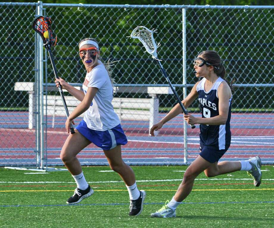Danburys Victoria Eanniello has possession of the ball while Staples Caitlin Hoberman follows close behind during a game at Danbury on Tuesday May, 20 2014. Photo: Lisa Weir / The News-Times Freelance