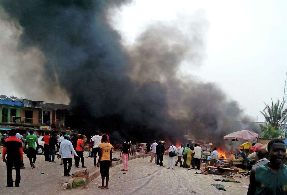 Smoke rises after a bomb blast at a bus terminal in Jos, Nigeria, Tuesday, May 20, 2014. Two explosions ripped through a bustling bus terminal and market frequented by thousands of people in Nigeria's central city of Jos on Tuesday afternoon, and police said there are an unknown number of casualties. The blasts could be heard miles away and clouds of black smoke rose above the city as firefighters and rescue workers struggled to reach the area as thousands of people fled. (AP Photo/Stefanos Foundation) ORG XMIT: AJOS102 / Stefanos Foundation
