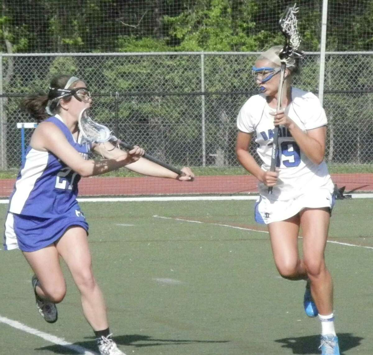 Fairfield Ludlowe senior defender Ellie Palazzo, left, pressures Darien's Jackie Brokaw (19) in the second half Tuesday, May 20 in an FCIAC girls lacrosse game at Darien. The Blue Wave defeated the Falcons 18-5. Brokaw had three assists.