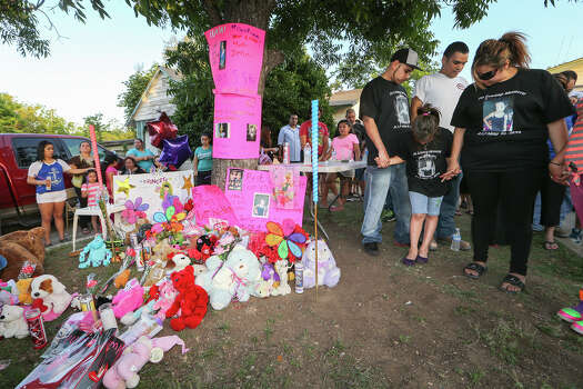 Jennifer DonJuan (from right, front), Jenabell Montana, 8, and Johnny Montana, pray with family, neighbors and  friends during a candellight vigil for six-year-old Jennilynn Montana at 1444 Aransas on Tuesday, May 20, 2014.  Jennilyn was a victiim of an accidental shooting at the residence on Sunday, MARVIN PFEIFFER/ mpfeiffer@express-news.net Photo: MARVIN PFEIFFER, Marvin Pfeiffer/ EN Communities / Express-News 2014