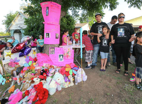 Jennifer DonJuan (from right, front), Jenabell Montana, 8, and Johnny Montana, stand with family, neighbors and  friends during a candellight vigil for six-year-old Jennilynn Montana at 1444 Aransas on Tuesday, May 20, 2014.  Jennilyn was a victiim of an accidental shooting at the residence on Sunday, MARVIN PFEIFFER/ mpfeiffer@express-news.net Photo: MARVIN PFEIFFER, Marvin Pfeiffer/ EN Communities / Express-News 2014