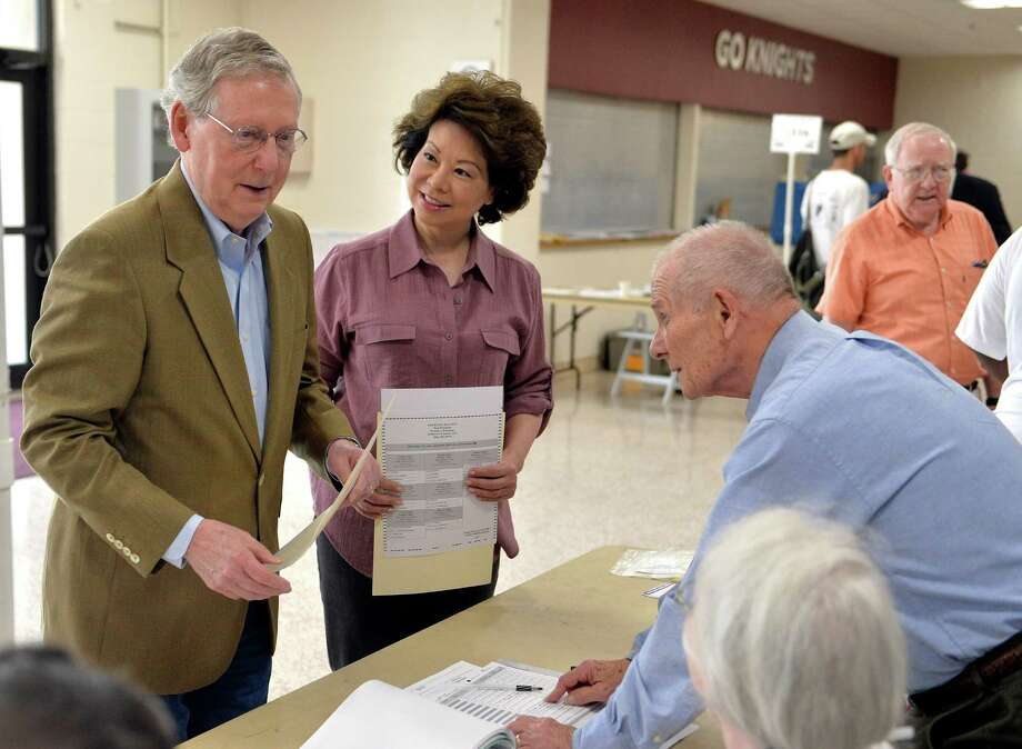 Kentucky Republican Senator Mitch McConnell, left, and his wife Elaine Chao, center, talk with poll workers as they sign in at their precinct Tuesday, May 20, 2014, at Bellarmine University in Louisville, Ky.  Ten months and $12 million later, Kentucky Republicans will put an end the fight Tuesday between  McConnell and Matt Bevin in a Republican Senate primary that failed to live up to its pre-election buzz. (AP Photo/Timothy D. Easley) ORG XMIT: KYTE108 Photo: Timothy D. Easley / FR43398 AP
