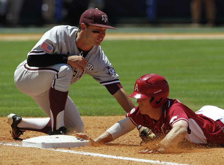 Arkansas' Brian Anderson (1) beats the tag from Texas A&M's Cole Lankford (12) at first base during the fourth inning at the Southeastern Conference NCAA college baseball tournament on Tuesday, May 20, 2014, in Hoover, Ala. (AP Photo/Butch Dill) Photo: Butch Dill, Associated Press / FR111446 AP